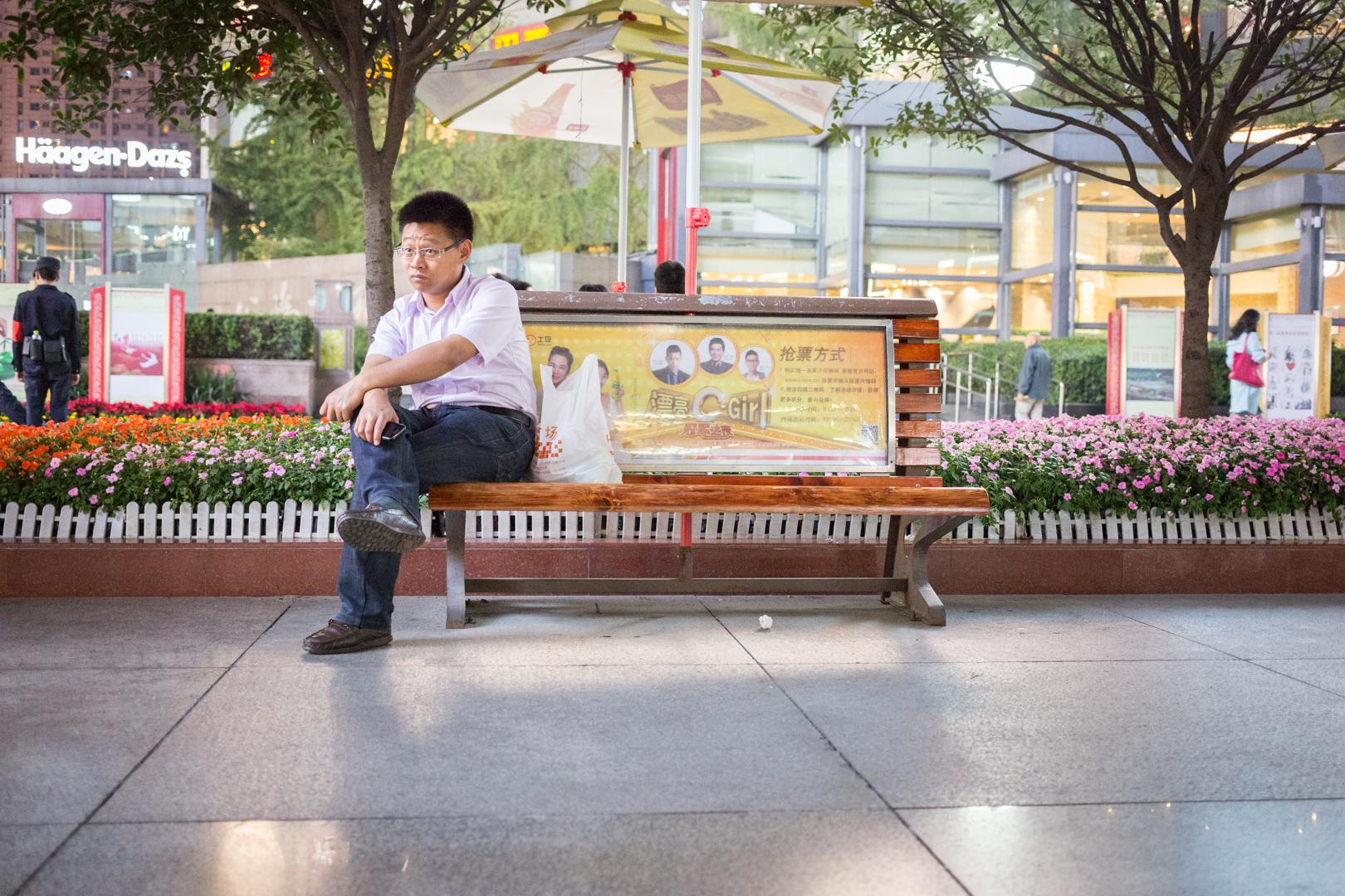 Man auf einer Bank in Chengdu, China